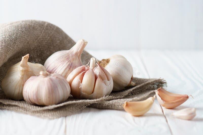 Aglio e chiodi di garofano di aglio su tela sulla tavola di legno bianca immagini stock