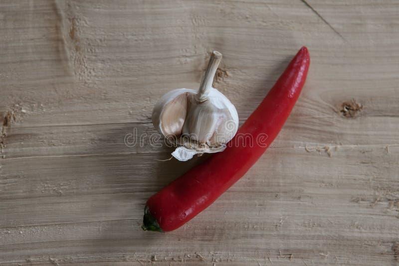 Aglio e peperoncino rosso su un pezzo di legno immagini stock