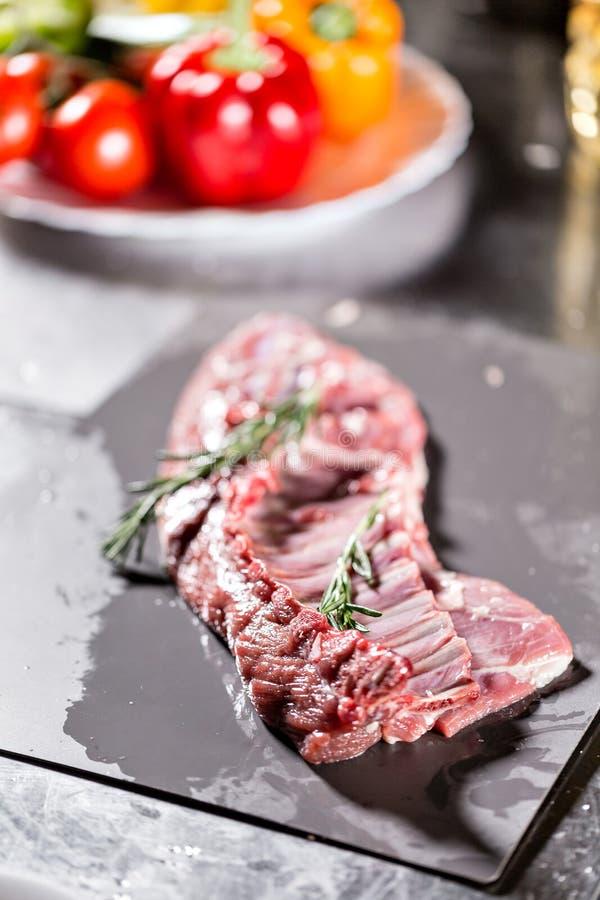 Agneaux rares prêts pour la marinade avec le romarin Cuisson avec le feu dans la poêle Chef professionnel dans une cuisine de images libres de droits