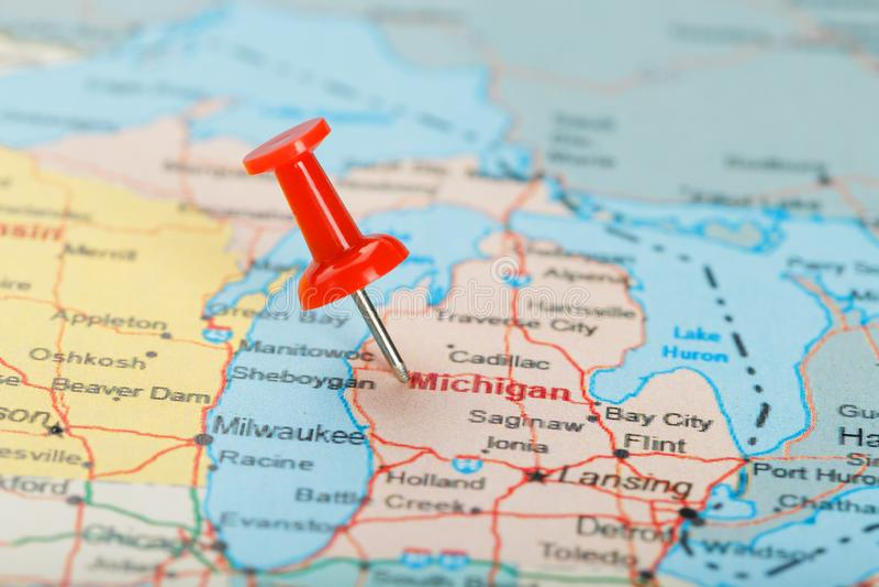 Ago d'ufficio rosso su una mappa di U.S.A., del Michigan e della capitale Lansing Mappa alta vicina del Michigan con la puntina r fotografia stock libera da diritti