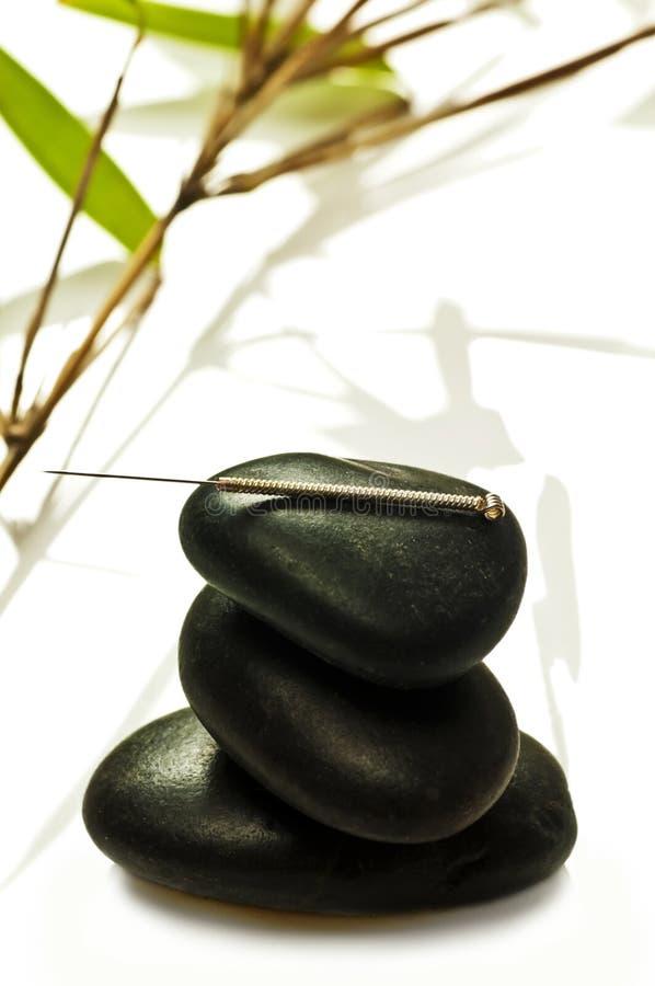 Ago di agopuntura sulla pietra fotografie stock libere da diritti