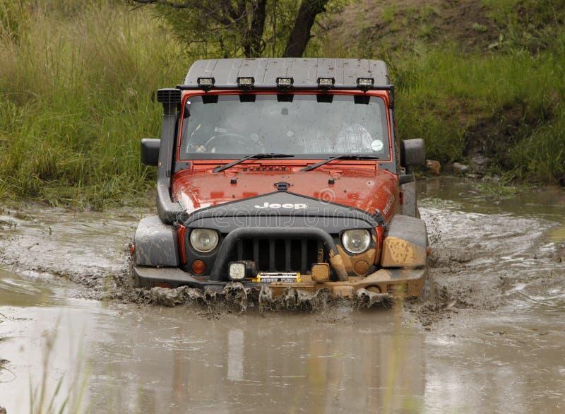 Agolpamiento Jeep Rubicon anaranjado que cruza la charca fangosa fotos de archivo libres de regalías