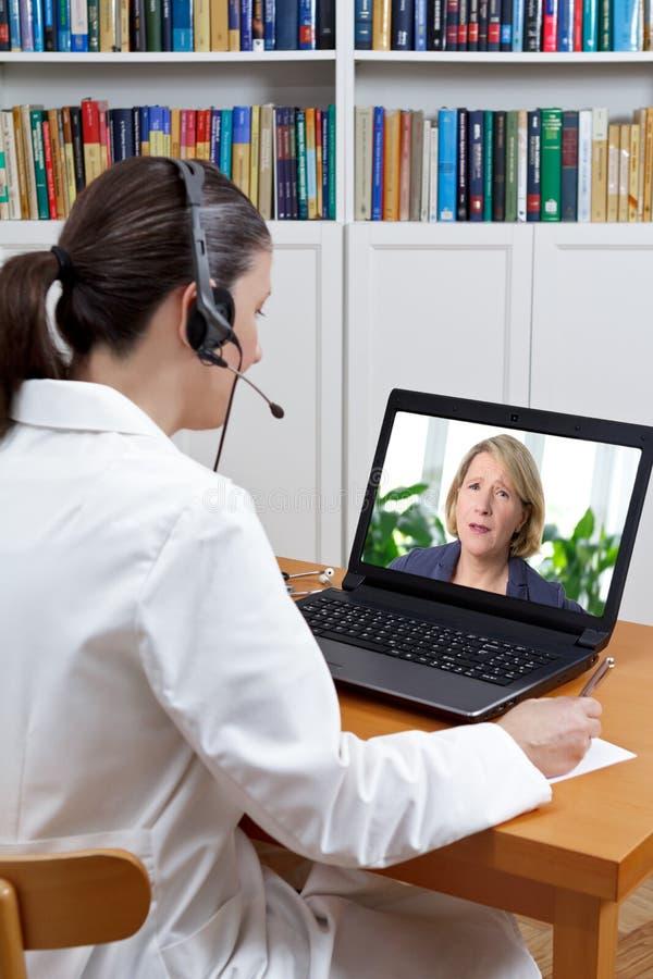Agonía del paciente del ordenador portátil de los auriculares del doctor fotografía de archivo libre de regalías