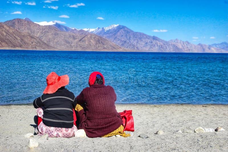 Agosto 2018, lago Pangong, Kashmir, India due turisti che si siedono accanto al pangong del lago durante il giorno davanti alle a immagine stock