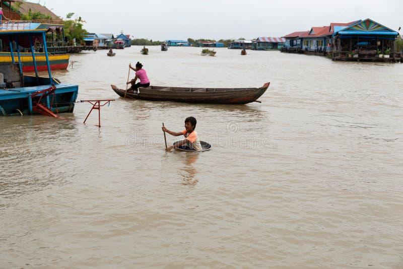 Agosto: 29: 2018 - SIEM REAP, CAMBOYA - madres e hijos en el barco con el lavabo del uso del muchacho como barco en el lago sap d fotografía de archivo