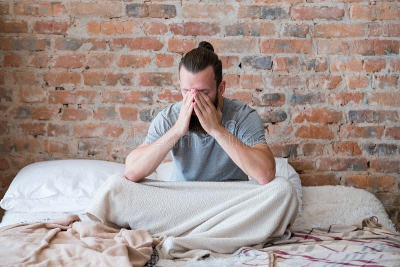 Agotamiento cansado de la mirada de la cama del hombre de la mañana de Omg imagenes de archivo