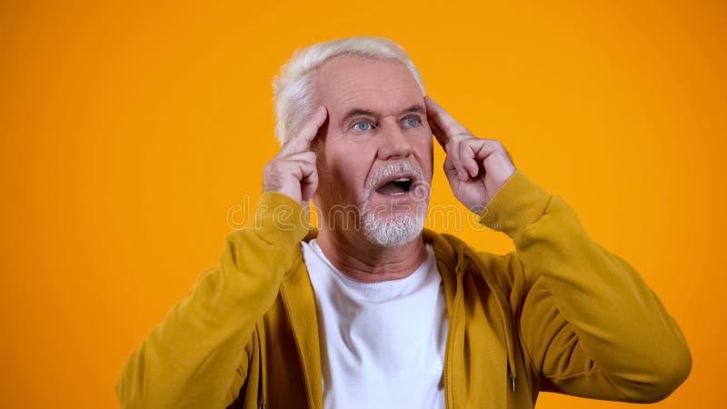 Agréable magicien vieilli touchant les temples, développant des capacités d'esprit télépathique images stock