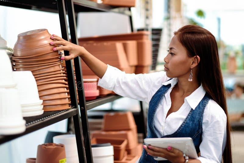 Agrônomo asiático bonito novo da mulher com a tabuleta que trabalha na estufa que verifica o inventário do armazenamento fotografia de stock royalty free