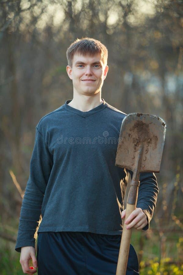 Agrônomo belo homem forte com pá sobre fundo em canteiros de flores imagem de stock