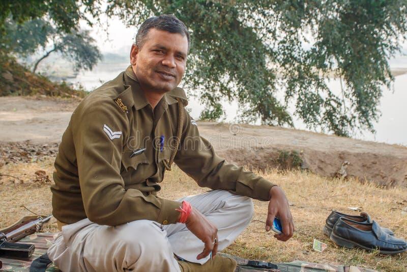 AGRA, ÍNDIA - EM DEZEMBRO DE 2012: Agente da polícia indiano que olha a câmera em um banco de rio imagem de stock