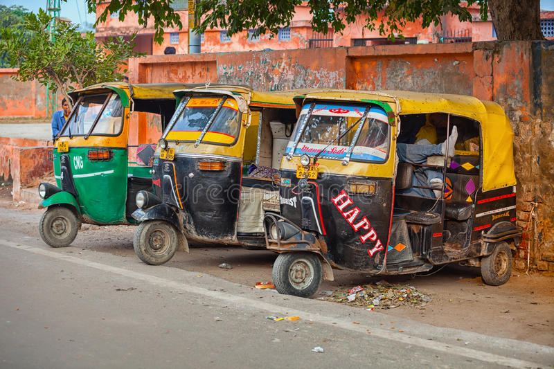 AGRA, INDIA - CIRCA NOV 2012: Three, colorfully painted, motorized rickshaws, parked in the shade on the shoulder of a typical st. Reet in Agra, India royalty free stock photo