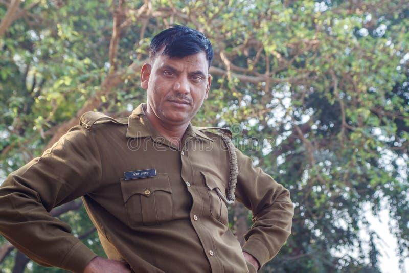 AGRA INDIA, GRUDZIEŃ, - 2012: Indiański funkcjonariusz policji patrzeje kamerę na brzeg rzeki obrazy stock