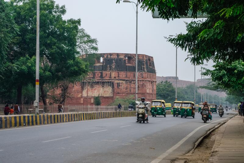 Tuk tuk taxis and bikes traffic and walls of the Red Fort of Agra at background, India. UNESCO World Heritage site royalty free stock images