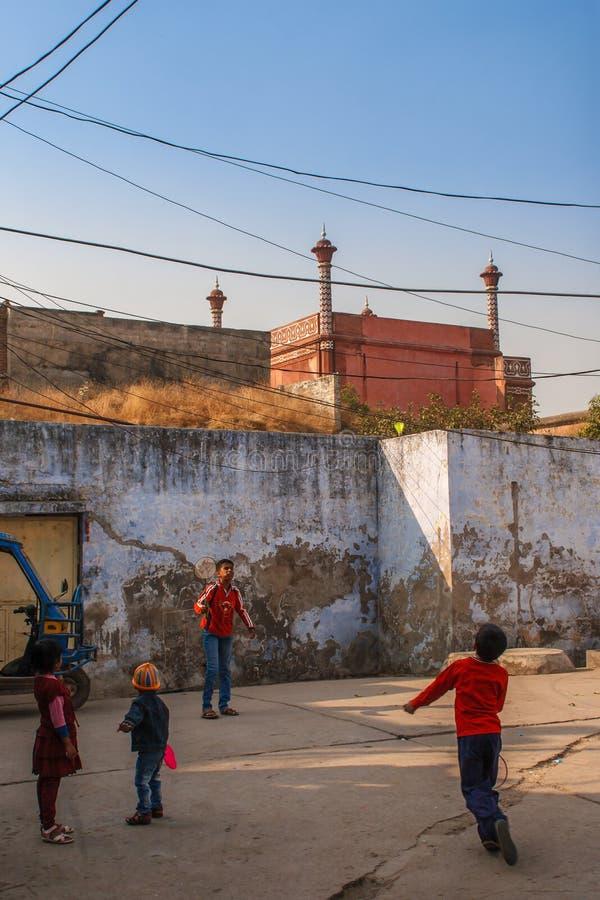 AGRA INDIEN - DECEMBER 2012: Taj Mahal staket och ungar som spelar badminton nära denna under av världen En av mest arkivfoton