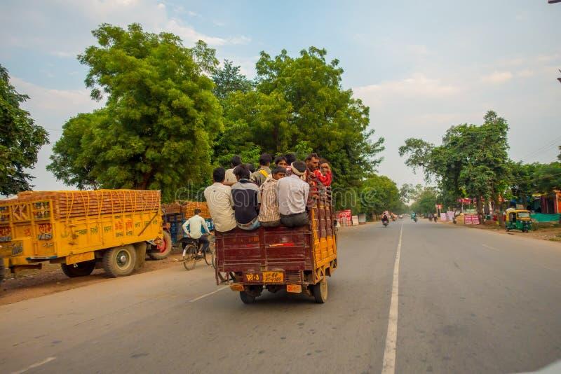AGRA, LA INDIA - 19 DE SEPTIEMBRE DE 2017: Muchedumbre de gente en la pieza trasera de un coche en las calles en ciudad central e imagen de archivo libre de regalías