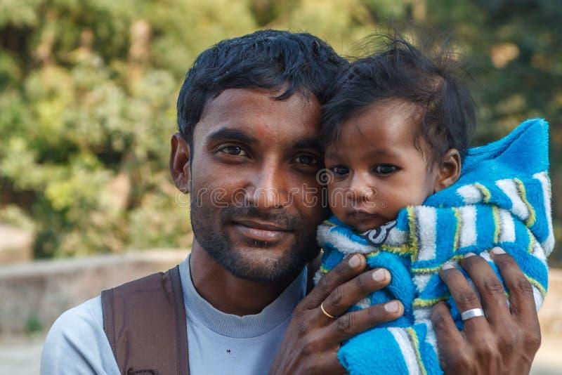 AGRA, LA INDIA - DICIEMBRE DE 2012: Familia india, padre que detiene a la hija en su revestimiento fotos de archivo libres de regalías