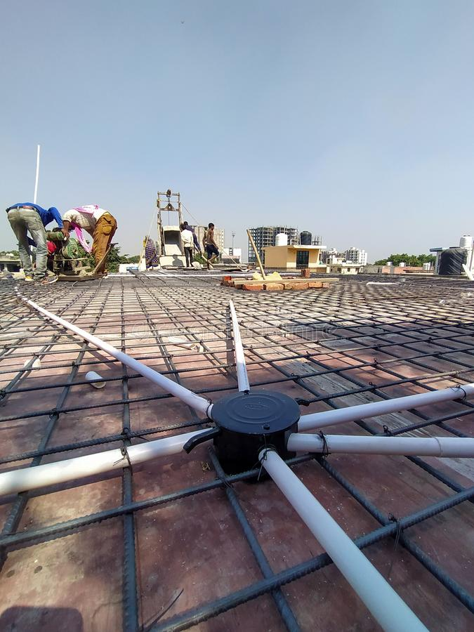 Agra- up- India- November 4, construction on the roof top, iron rod and electronic pipe spread all over the roof, people working royalty free stock images