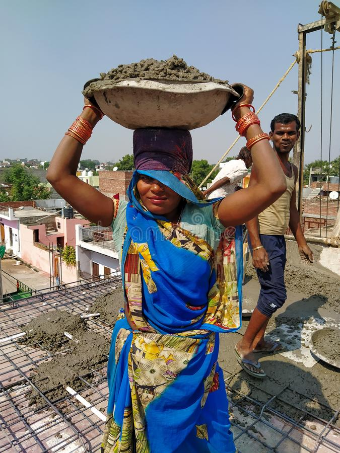 Agra- up- India- November 4, an indian women standing and holding cement bowl at the construction site stock image