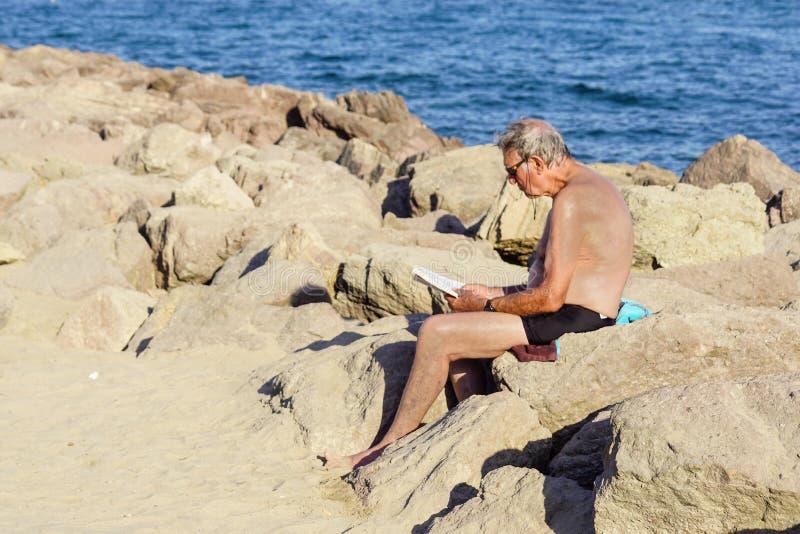 Agradável, França - 5 de agosto de 2017: opinião o homem que senta-se nas rochas que relaxam e lidas um livro na praia fotografia de stock royalty free