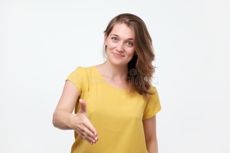 Agradável para encontrá-lo Retrato do aperto de mão da jovem mulher emocional bonita no t-shirt amarelo fotografia de stock