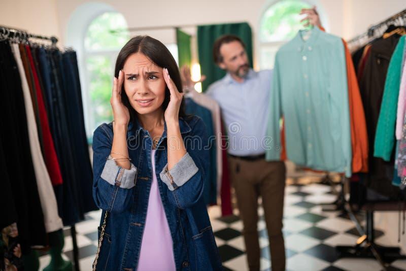 Agradável-vista fêmea tendo a dor de cabeça ao comprar com um esposo imagem de stock royalty free