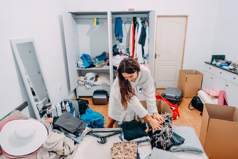 Agrad?vel-olhando a senhora dentro da sala moderna do apartamento para preparar-se para trope?ar imagem de stock royalty free