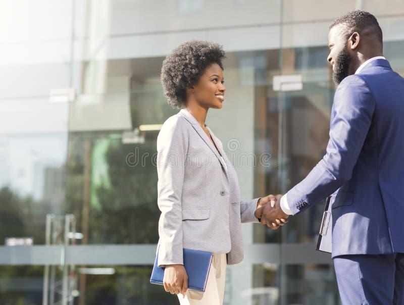 Agradable encontrarle Dos hombres de negocios africanos que introducen al aire libre imagenes de archivo