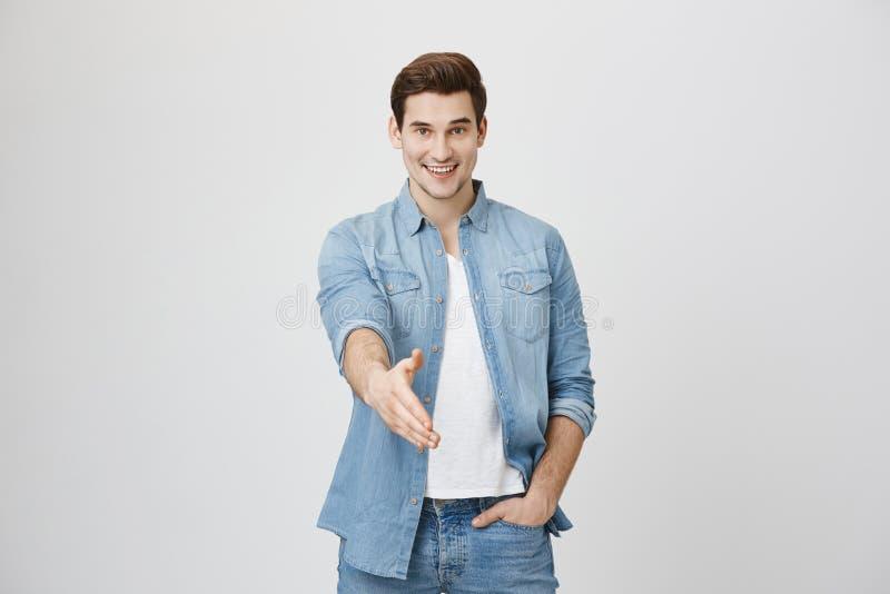 Agradable joven apuesto que estira el brazo con gesto de bienvenida, usando camisa de denim y sonriendo ampliamente, aislado imagen de archivo