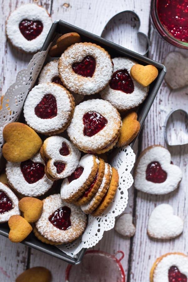 Agradables galletas con forma de lino en forma de corazón con mermelada de frambuesa Cerrar Concepto de horneado casero imágenes de archivo libres de regalías