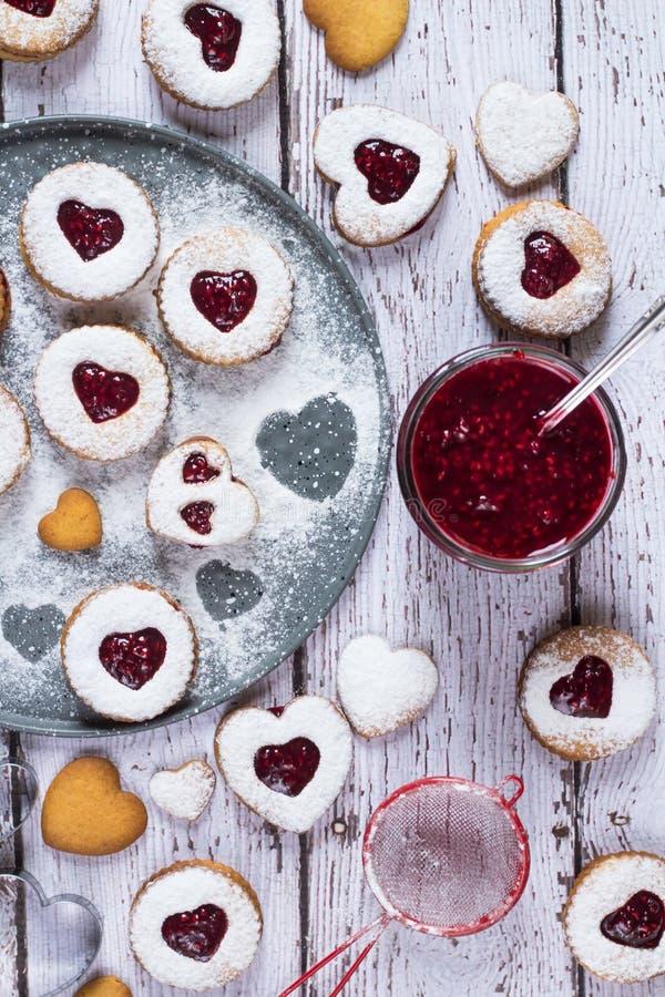 Agradables galletas con forma de lino en forma de corazón con mermelada de frambuesa Cerrar Concepto de horneado casero fotografía de archivo libre de regalías