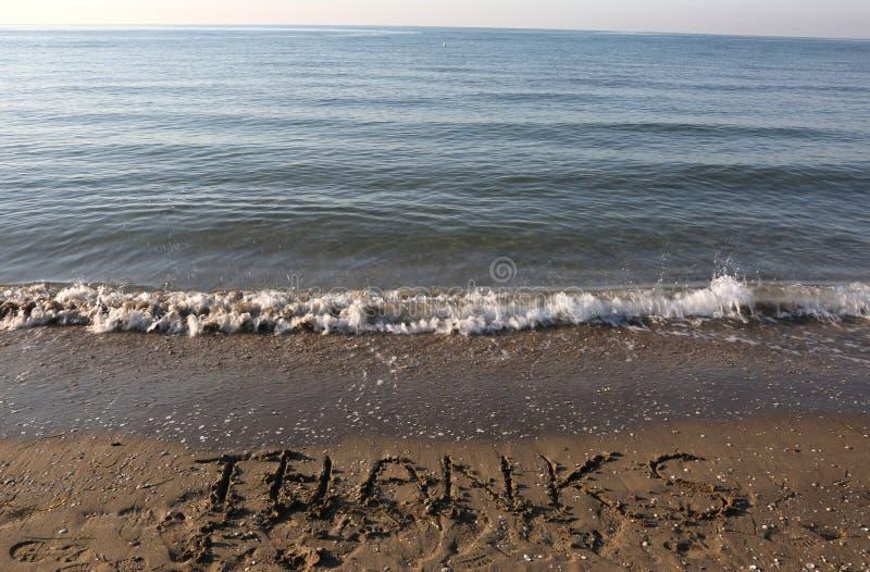 AGRADECIMENTOS do texto na areia da praia imagem de stock