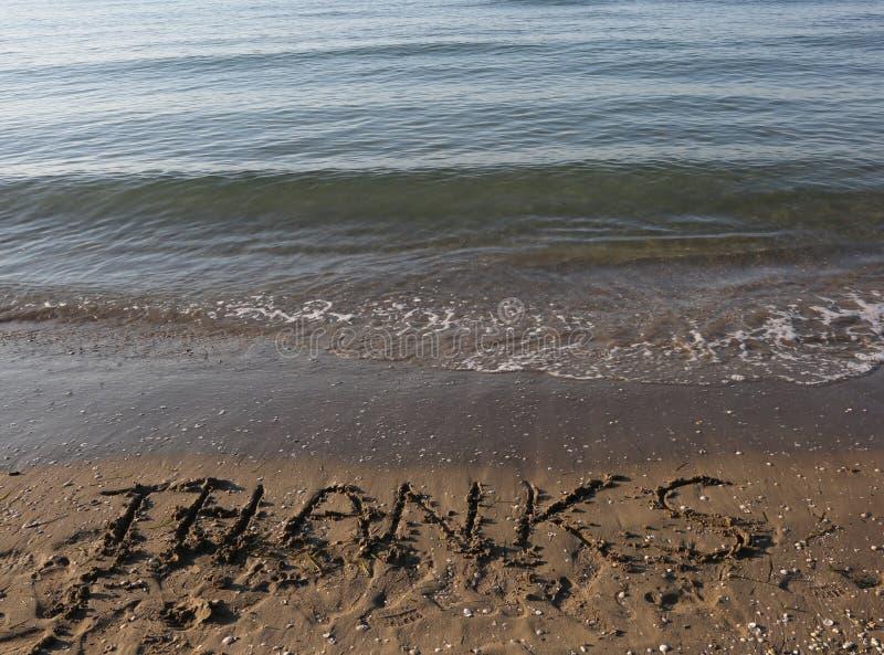 AGRADECIMENTOS do texto na areia no verão imagens de stock