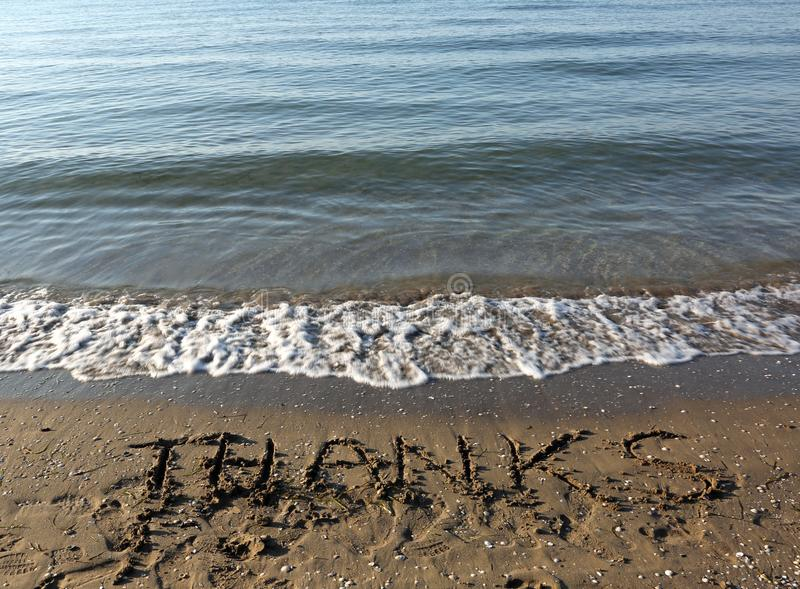 AGRADECIMENTOS grandes do texto na areia da praia fotografia de stock royalty free