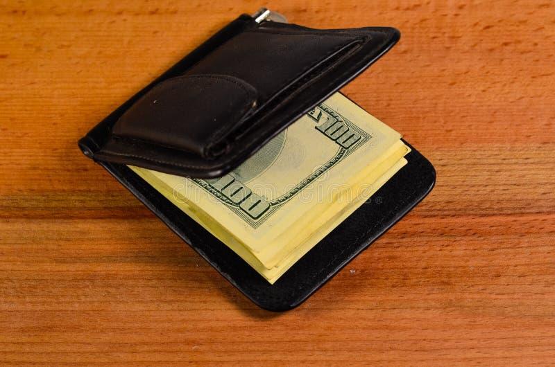 Agrafe d'argent avec cent dollars de billets de banque sur la table en bois photos stock