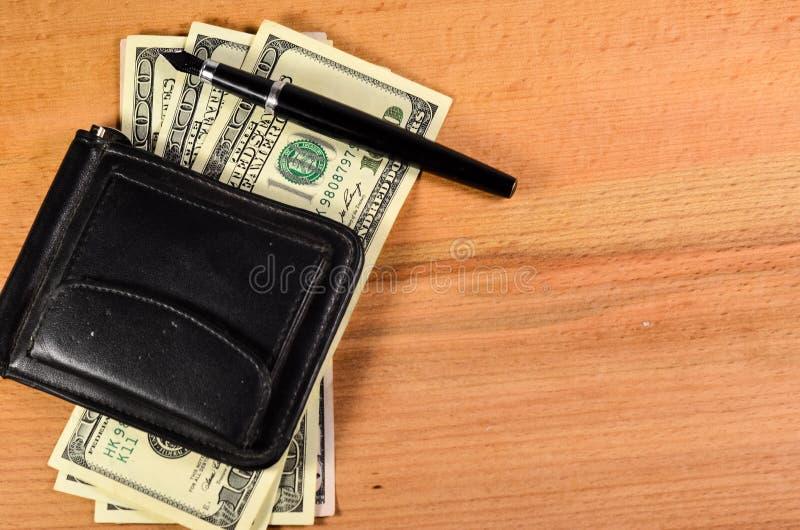 Agrafe d'argent et cent dollars de billets de banque sur la table en bois photographie stock