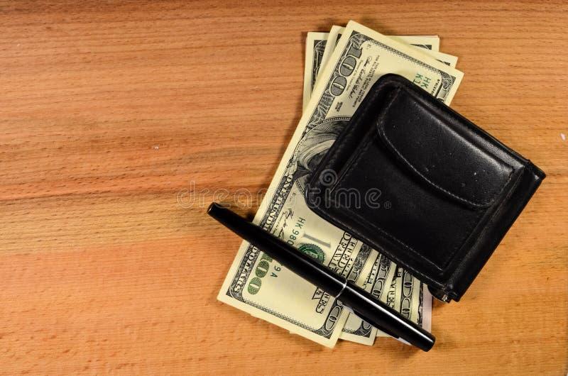 Agrafe d'argent et cent dollars de billets de banque sur la table en bois photo libre de droits