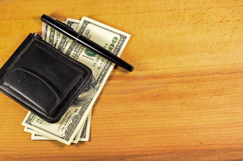 Agrafe d'argent et cent dollars de billets de banque sur la table en bois image libre de droits