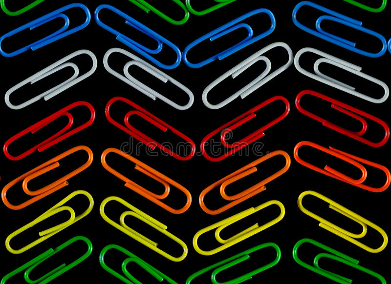 Agrafes de couleur sur un fond noir Configuration sans joint images libres de droits