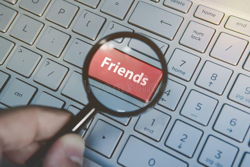 Agrandado a través de amigos dominantes rojos de la lupa en fondo del teclado Búsqueda en línea para los amigos Una persona utili imagen de archivo