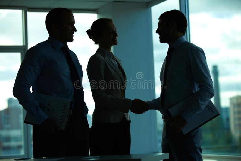 Agreement in dark office stock image