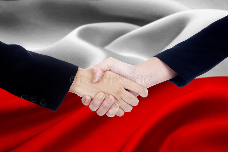 Agreement handshake with flag of Poland. Photo of agreement handshake with two entrepreneur hands, shaking hands with a Poland flag background stock image