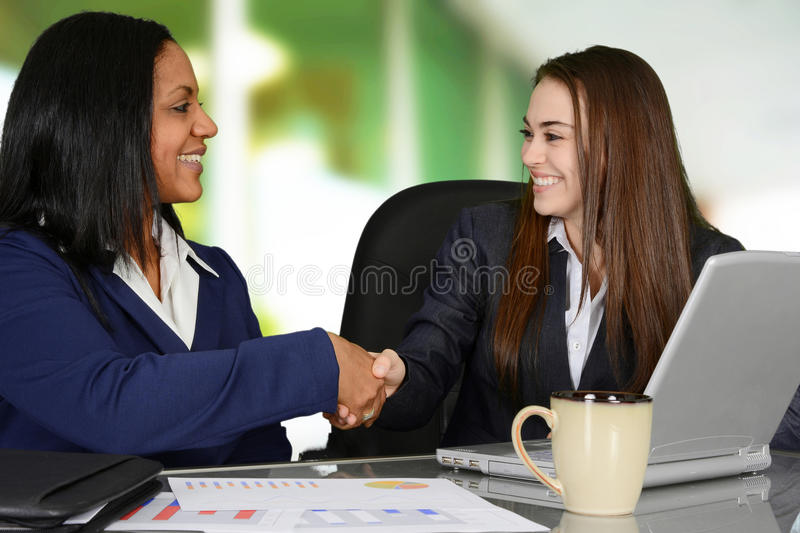 Agreement. A handshake between two female co-workers in the office royalty free stock photos