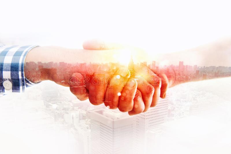 Handshaking business person in casual wear. concept of teamwork and partnership. double exposure royalty free stock photo
