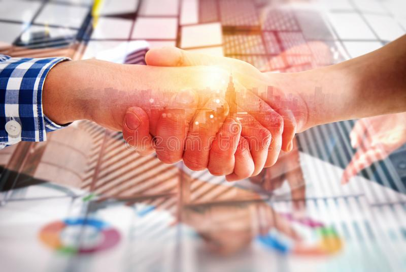 Handshaking business person in casual wear. concept of teamwork and partnership. double exposure. Agreement between young business people with light effects stock images