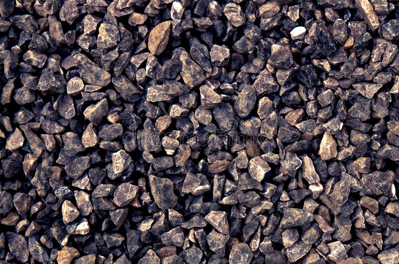 Agregado das pedras cinzentas grosseiras escuras esmagadas em um poço de pedra - cobrir o teste padrão fotografia de stock