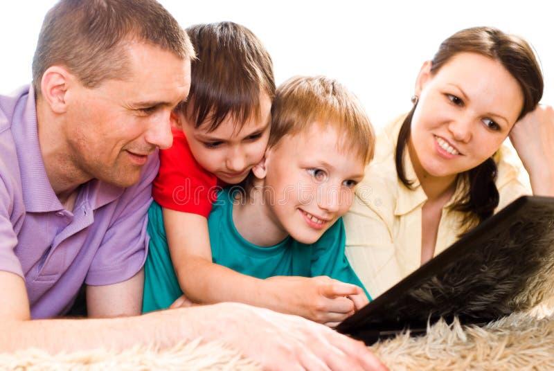 Agregado familiar com quatro membros com um portátil imagens de stock