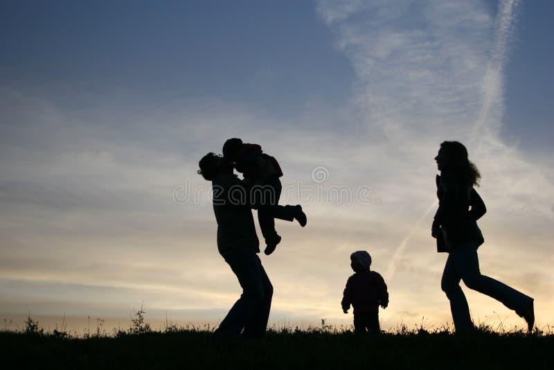 Agregado familiar com quatro membros da silhueta fotografia de stock