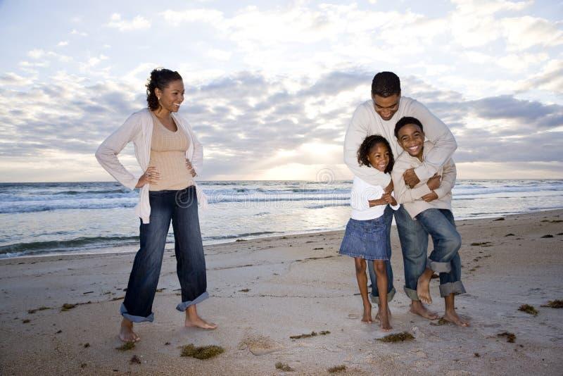 Agregado familiar com quatro membros feliz do African-American na praia foto de stock royalty free