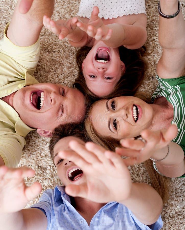 Agregado familiar com quatro membros feliz que encontra-se no tapete fotografia de stock royalty free