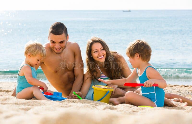 Agregado familiar com quatro membros na praia foto de stock royalty free